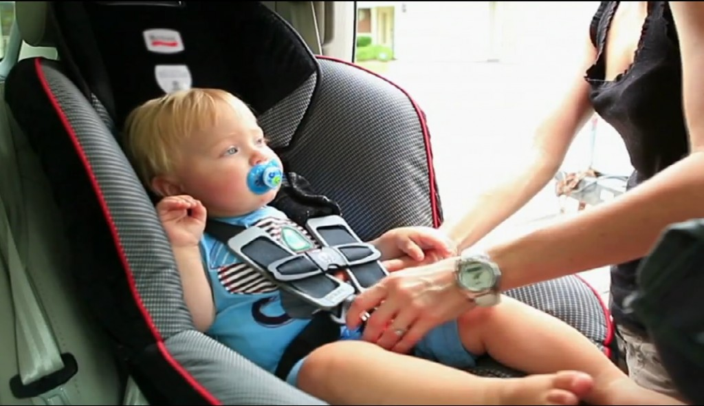 Toddler in car seat being buckled in by mom baby carseat safety