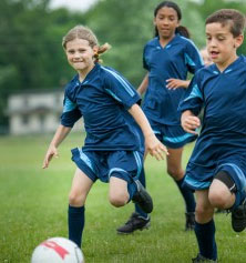 girl and boy playing soccer