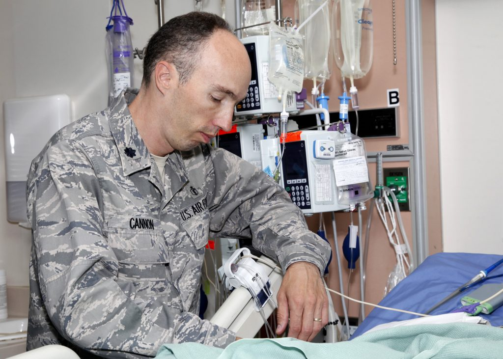 "Air Force Lt. Col. (Dr.) Jeremy Cannon checks on a critically injured patient at the San Antonio Military Medical Center intensive care unit, Ft. Sam Houston, Texas. Dr. Cannon, chief of trauma and acute care surgery at SAMMC and assigned to the 59th Medical Wing, is the guest editor of the August edition of the ""Surgical Clinics of North America."" (U.S. Army photo/Dwayne R. Snader)"